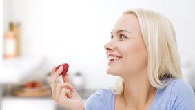 Mujer feliz que come la fresa en cocina Imagen de archivo libre de regalías