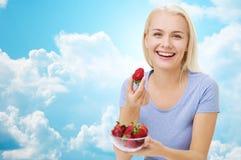 Mujer feliz que come la fresa sobre el cielo Foto de archivo libre de regalías