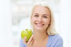 Mujer feliz que come la manzana verde en casa Fotografía de archivo