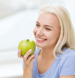 Mujer feliz que come la manzana verde en casa Fotografía de archivo libre de regalías