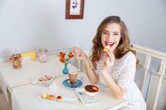 Mujer feliz que come las pequeñas tortas y que bebe el latte en café Foto de archivo libre de regalías