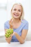 Mujer feliz que come las uvas en casa Imagenes de archivo