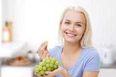 Mujer feliz que come las uvas en cocina Foto de archivo