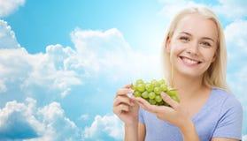 Mujer feliz que come las uvas sobre el cielo Imagenes de archivo