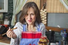Mujer feliz que come relevo de los frutos secos y de la miel Fotografía de archivo libre de regalías