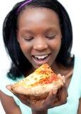 Mujer feliz que come una pizza Foto de archivo