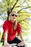 Mujer feliz que completa un ciclo en la bicicleta Imagen de archivo