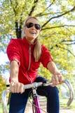 Mujer feliz que completa un ciclo en la bicicleta en parque fotografía de archivo libre de regalías