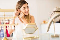 Mujer feliz que compra un poco de joyería foto de archivo