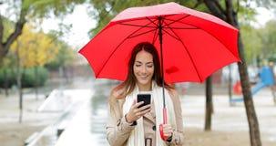 Mujer feliz que comprueba el teléfono debajo de la lluvia