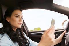 Mujer feliz que conduce el coche con smarhphone fotos de archivo