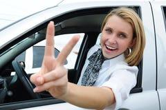 Mujer feliz que conduce un nuevo coche Imágenes de archivo libres de regalías