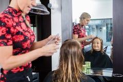 Mujer feliz que consigue corte de pelo en salón de belleza imágenes de archivo libres de regalías