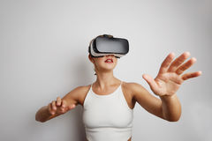 Mujer feliz que consigue experiencia usando los vidrios de las auriculares de VR de realidad virtual en casa muchas las manos que Fotos de archivo