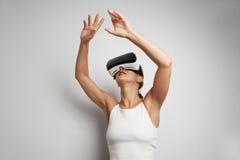 Mujer feliz que consigue experiencia usando los vidrios de las auriculares de VR de realidad virtual en casa muchas las manos que Imagen de archivo libre de regalías