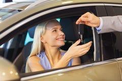 Mujer feliz que consigue llave del coche en salón del automóvil o salón Fotos de archivo