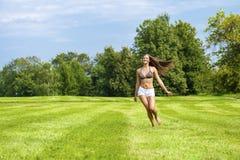 Mujer feliz que corre en campo de hierba del verano o de la primavera Imagen de archivo libre de regalías