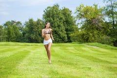 Mujer feliz que corre en campo de hierba del verano o de la primavera Imágenes de archivo libres de regalías