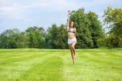 Mujer feliz que corre en campo de hierba del verano o de la primavera Fotografía de archivo