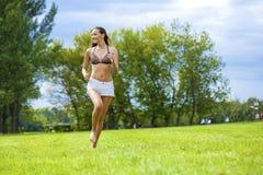 Mujer feliz que corre en campo de hierba del verano o de la primavera Fotos de archivo libres de regalías
