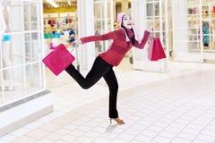 Mujer feliz que corre en centro comercial Fotos de archivo
