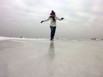 Mujer feliz que corre en el mar congelado al día frío imagen de archivo