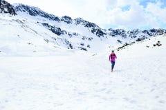 Mujer feliz que corre en montañas el día soleado del invierno fotos de archivo libres de regalías