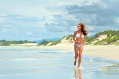 Mujer feliz que corre a lo largo de la playa Fotografía de archivo