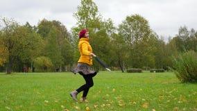 Mujer feliz que da vuelta alrededor y que hace girar en hojas de arce metrajes