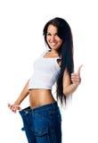Mujer feliz que demuestra pérdida de peso Fotografía de archivo libre de regalías