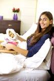 Mujer feliz que desayuna en cama Foto de archivo libre de regalías