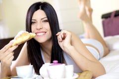 Mujer feliz que desayuna en cama en el país Imágenes de archivo libres de regalías