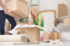 Mujer feliz que desempaqueta en nuevo hogar Imágenes de archivo libres de regalías