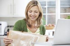 Mujer feliz que desempaqueta la compra en línea en casa Imagen de archivo