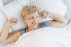 Mujer feliz que despierta en cama Fotos de archivo libres de regalías