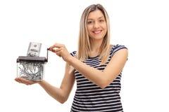 Mujer feliz que destruye un billete de banco del dólar en una trituradora de papel Fotografía de archivo