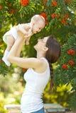 Mujer feliz que detiene en brazo a un bebé en un jardín Fotografía de archivo