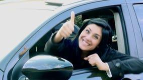 Mujer feliz que dice hola del pulgar del coche para arriba metrajes
