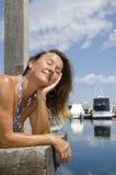 Mujer feliz que disfruta de día asoleado en el puerto deportivo Imagenes de archivo