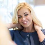 Mujer feliz que elige el colgante en la joyería fotografía de archivo