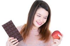 Mujer feliz que elige entre el chocolate oscuro y la fruta roja de la manzana sobre el fondo blanco fotos de archivo