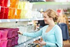 Mujer feliz que elige la maceta en tienda Imagenes de archivo