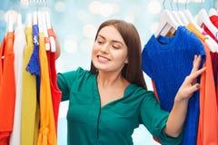 Mujer feliz que elige la ropa en el guardarropa Imagenes de archivo