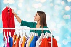 Mujer feliz que elige la ropa en el guardarropa Imagen de archivo