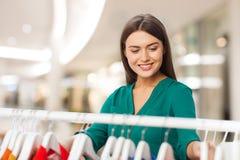 Mujer feliz que elige la ropa en la alameda de compras Fotografía de archivo libre de regalías