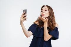 Mujer feliz que envía un beso y que toma el selfie con smatphone Imagen de archivo