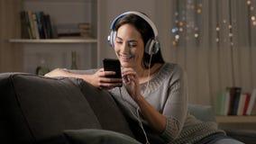 Mujer feliz que escucha la música en el teléfono en la noche metrajes