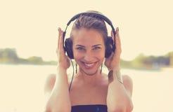 Mujer feliz que escucha la música en los auriculares al aire libre por el lago imagenes de archivo