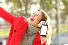 Mujer feliz que escucha la música y que muestra el teléfono Fotografía de archivo