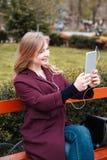 Mujer feliz que escucha la música y que hace el selfie usando la tableta Imagen de archivo